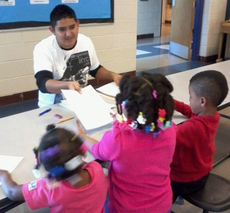 Journalism major Bernanrdo Frias works with students from Crow Elementary in Arlington. Frias and several other Department of Communication students volunteered this semester with the Reading Corps. (Photo contributed)
