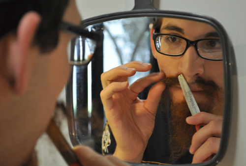 Theatre Arts senior Joshua Equia makes final adjustments to his prop mustache and beard before presenting himself to Associate Professor Joe Kongevick and his fellow students in this summer's Theatrical Makeup class. The course enables students to create realistic prosthetics and special effects for stage and film actors. (Photo by James Dunning)