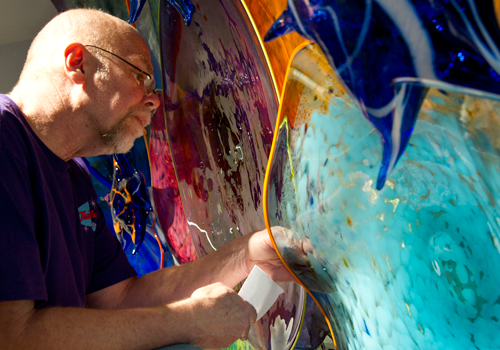 David Keens works on a glass piece at the College Park Center before it opened in 2011. (Photo credit: Beth McHenry/University Communications)