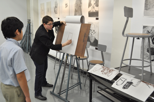 Lecturer H. Schenck, second from left, demonstrate a drawing technique during the Department of Art & Art History's open house Jan. 31.