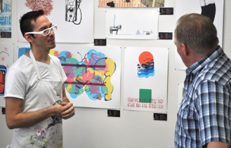 Graduate student David Diaz, left, talks about printmaking techniques during the Department of Art & Art History's open house Jan. 31.