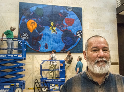 Workers install a painting by Art professor Benito Huerta (right) in the atrium of the Amon Carter Museum of American Art. (Photo by ACM)