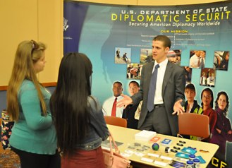 Joshua Bauer, right, talks to students about the U.S. Department of State's Diplomatic Security division during the Department of Criminology & Criminal Justice Career Fair on April 16. The event was sponsored by the Alpha Phi Sigma Honor Society. (Photo by James Dunning)