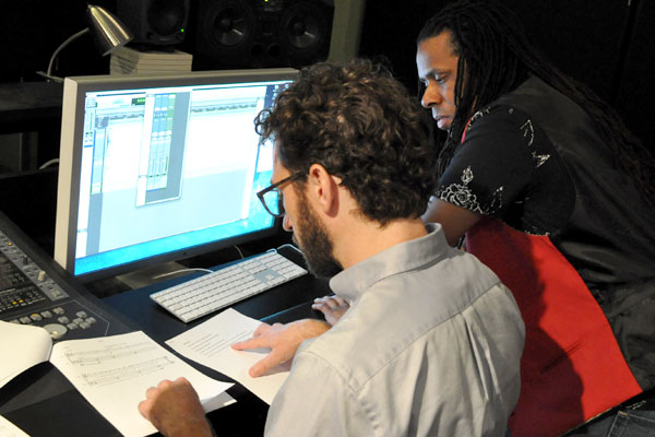 Assistant Professor Ya'Ke Smith (Art & Art History), right, and Senior Lecturer Micah Hayes (Music) discuss the film score for Smith's new short film at Studio 360 on May 2. (Photo by James Dunning/COLA)