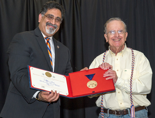 UTA President Vistasp Karbhari, left, hands Associate Professor Allan Saxe (Political Science) his UT System Board of Regents' Outstanding Teaching Award earlier this month in a special faculty meeting. (Photo by Beth McHenry/University Communications)