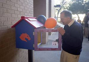 Associate Professor Allan Saxe (Political Science) inspects a free library kiosk, one of three recently added to the UT Arlington campus. Saxe donated funds to build the small library stands. (Photo contributed)