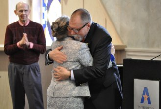 Karl Petruso (right), professor of anthropology and Dean of the Honors College, hugs Dr. Beth Wright, former Dean of Liberal Arts, greets colleagues and well-wishers at a special reception Jan. 30, 2015, in the E.H. Hereford University Center. English Professor Ken Roemer, left, looks on. (Photo by James Dunning/COLA Communications)