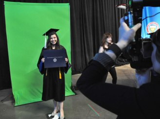 During the College of Liberal Arts' Spring 2015 Commencement at College Park Center on Friday, May 15, students pose for official photos. (Photo by James Dunning/COLA Communications)