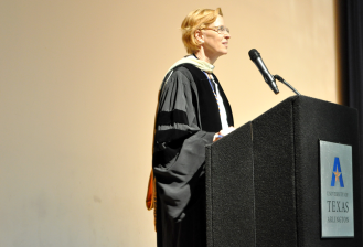 Associate Dean Elisabeth Caution address graduates and their families at the College of Liberal Arts master's hooding ceremony May 15 in the Mavericks Activity Center. (Photo by James Dunning/COLA Communications)