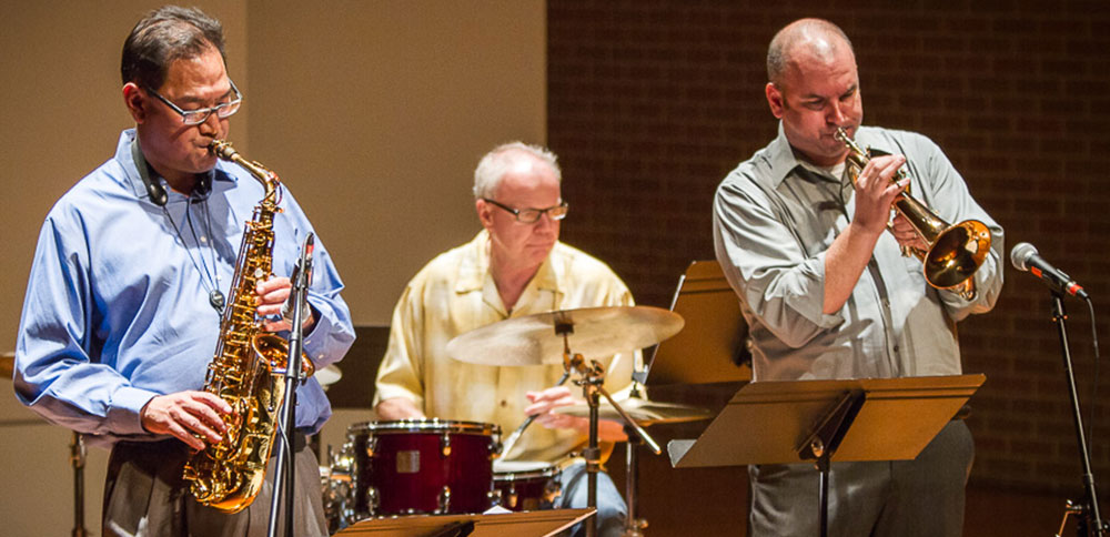 Associate Professor Tim Ishii, left, Mike Drake, center, and Adjunct Instructor Ken Edwards, right, perform during a faculty jazz recital earlier this month with pianist Stefan Karlsson. (Photo by Jack Unzicker)