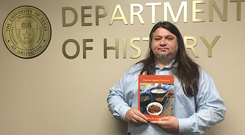 Doctoral student Robert Caldwell poses with a copy of his new book, Choctaw-Apache Foodways (Texas A&M University Press). The book explores food influences on tribes for more than 200 years.